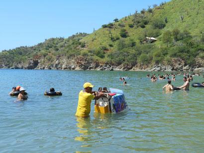 Der Eisverkäufer versucht im Wasser seine Ware an den Mann zu bringen