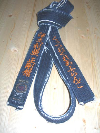 Cintura nera consegnata da Sensei Sadanobu Tatsuto a            Sensei Francesco Cuzzocrea  con  su  scritto  Italia  Seigokan  a sinistra ed  a  destra  Francesco  Cuzzocrea