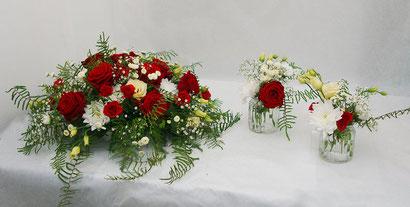 Tischgesteck und kleine Vasen mit roten Rosen
