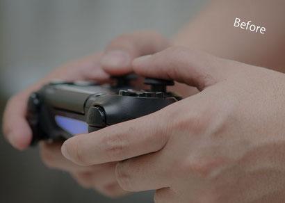 ゲームコントローラーを持つ少年の手