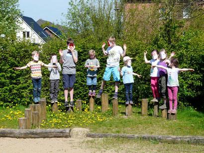 """10 kleine """"Stieglitze"""" mit selbst angemalten Masken des """"Vogel des Jahres"""" flogen über den Spielplatz."""