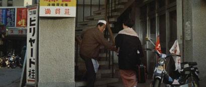 ▲階段を上る久造。「満貫荘」はどうやら2階にあるようだ。(画像③)