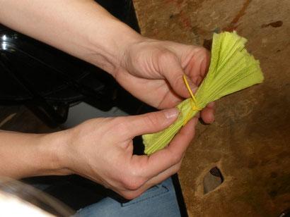 Wenn alles gefaltet ist, nehmt ihr euch einen Gummi. Diesen wickelt ihr ein paar mal in der Mitte um die Serviette. Ihr könnt ihn aber auch zerreissen und um die Mitte der Serviette knoten. Am Besten macht ihr das mit einem Doppelknoten.