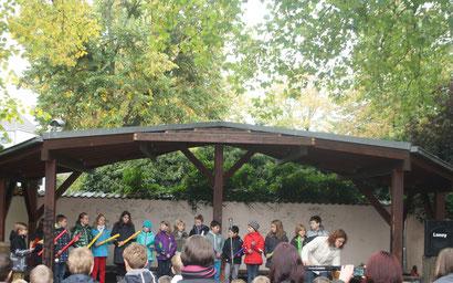 Die Klasse 4b auf der Schulhofbühne mit dem Dracula-Rock beim Herbstsingen