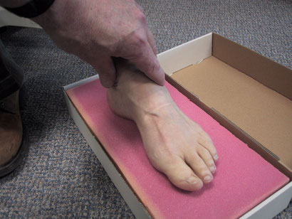 demonstrating how an imoression is taken of the foot