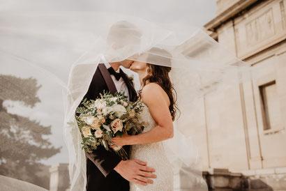 Ein Brautpaar küsst sich und wird dabei vom Schleier verdeckt. Währenddessen hält die Braut den Brautstrauß in der Hand.