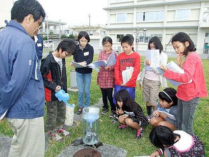 雨量計の仕組みについて学ぶ児童たち=26日午前、石垣島地方気象台