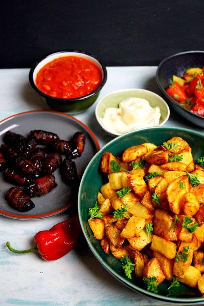 eine kleine Tapas-Auswahl mit Datteln in Bacon und Patatas bravas