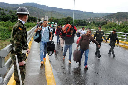 Colombians carrying government subsidized goods over the border