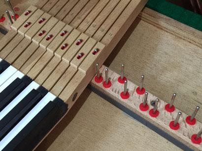 アップライトピアノの鍵盤とその下の金属部品やフェルトの状態を確認