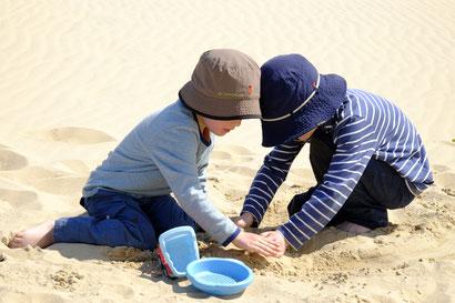 Mio und Lasse spielen im Sand