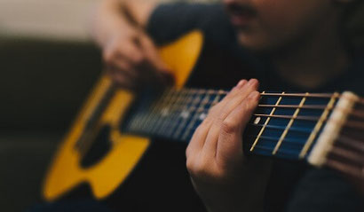 A man holding and playing a guitar. Playing guitar is a good, constructive form of distraction