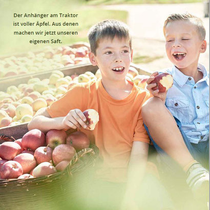 Zwei Jungs sitzen auf einem Traktor voller Äpfel und lassen sich die Äpfel schmecken