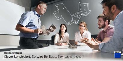 Das Bild zeigt eine Schulung mit fünf Personen, einer zeigt den anderen Bauteile aus Blech