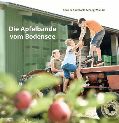 """Buchcover """"Die Apfelbande vom Bodensee"""" von Corinna Spitzbarth und Peggy Wandel, drei Kinder auf Traktor"""