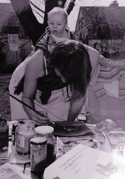 Dagmar mit Töchterchen Karla auf dem Rücken und beim Malen von 5 Möpsen auf einem Sofa... für eine Filmproduktion