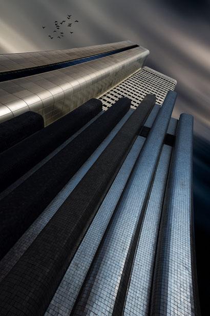 Dunkle Vision des DB Silver Tower in Frankfurt am Main mit Denkmal im Vordergrund und Vogelschwarm am Himmel