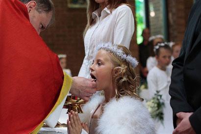 Foto eines Erstkommunionkindes, das die Hostie empfängt