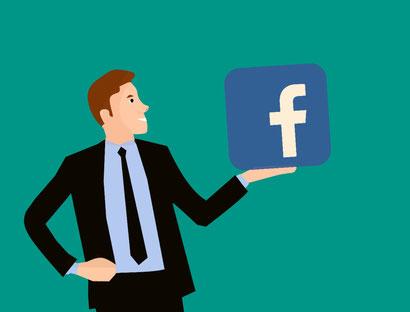 Man der das Facebook Symbol mit der linken Hand in die Luft hält