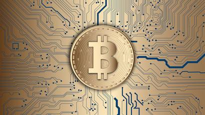 Auf dem Bild ist das Bitcoin Symbol auf einem Coin zu sehen