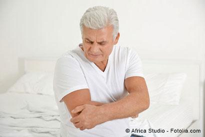 Älterer Mann hält sich nach dem Aufstehen aus dem Bett den Arm