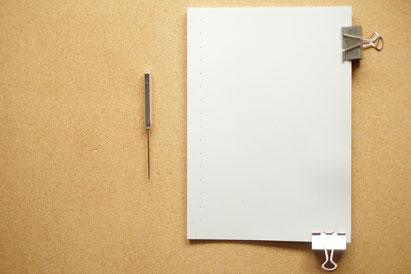 広島のイラストレーター、絵本作家の手製本で絵本を作る写真。裁断した紙をクリップで固定。