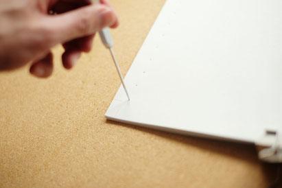 広島のイラストレーター、絵本作家の手製本で絵本を作る写真。鋭い針で穴を開ける。