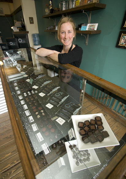 Woman shop owner with displays of gourmet chocolate in old style shop in Cumberland.