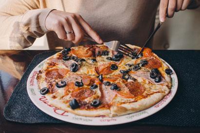 Pizza essen - Motiv aus einer Foto-Datenbank im Internet. Wahrscheinlich  ein sorgfältig ausgeleuchtetes Bild aus dem Fotostudio.