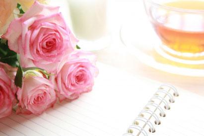 広げられたノートの上に無造作に置かれたピンクのバラのブーケ。紅茶の入ったカップ&ソーサ。