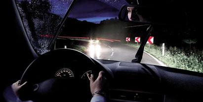Eine Frau fährt bei Nacht mit Ihrem Pkw um eine Kurve, als ihr jemand entgegen kommt. Die Scheinwerfer des entgegenkommenden Autos blenden, das Licht am Fahrzeug der Frau ist hell und geht mit der Kurve mit. / Bildquelle: BOSCH Service