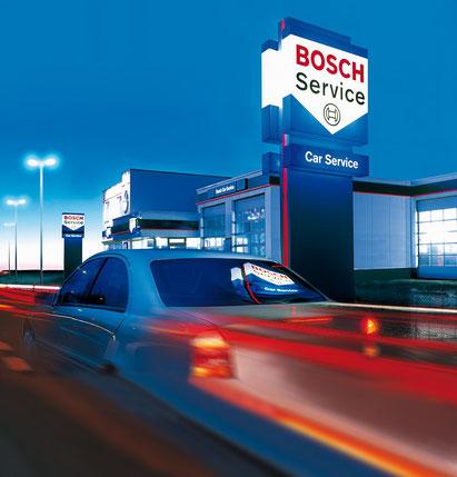 Ein Auto fährt am Abend an einer BOSCH Service Werkstatt vorbei.  / Bildquelle: BOSCH Service