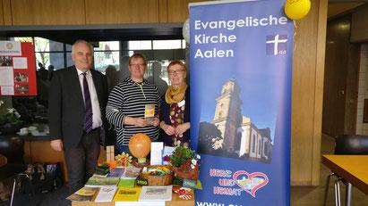 Birgit Rück, Susanne Fiedler und Pfarrer Bernhard Richter am Stand der Evang. Kirchengemeinde im Foyer des Rathauses.