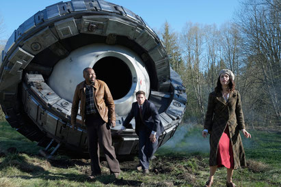 Image of main characters from the NBC show Timeless, standing in front of creepy looking Time Machine.