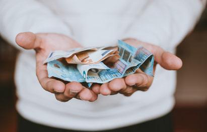Hand mit Geld von Spenden