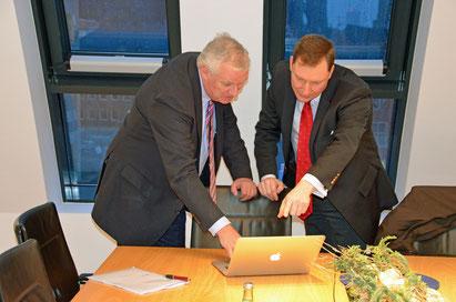 Die Gesellschafter der B-CONNECT Axel Woeller und Stephan Reinartz schauen gemeinsam auf einen Laptop