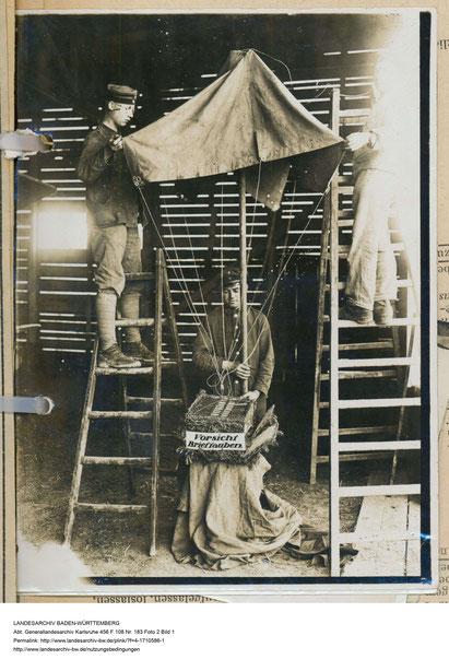 Soldaten beim Befestigen eines gepolsterten Weidenkorbs an einem Fallschirm für den Abwurf von Brieftauben