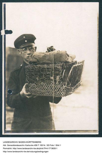 Foto eines Soldaten, der einen für den Flugzeugabwurf vorbereiteten, gepolsterten Taubenkorb trägt