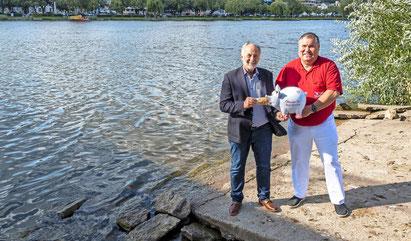 Klaus Bart (links) übergibt vor der Kulisse der Mosel in Nennig eine Spende in Höhe von 5000 Euro für das Hochwasser-hilfsprojekt der Merziger Herzensengel von Adrian Schmitz (rechts).