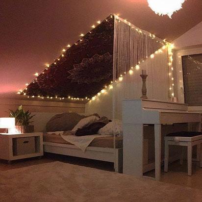 Großes Mandala Wandtuch in schwarz an der Wand hinter dem Bett