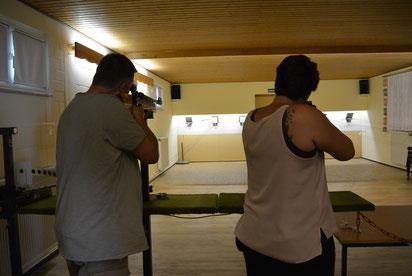 Viele Kinder und Erwachsene schießen mit Luft- oder Lichtpunktgewehr.