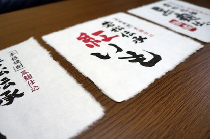 焼酎の容器に貼り付ける別注で作製した四方耳付きの手漉き和紙ラベルの使用例