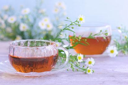 カモミールの花束とハーブティの入った耐熱ガラス製のカップ&ソーサ。