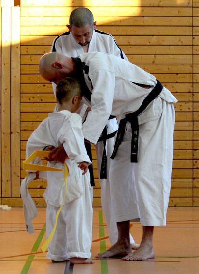 Das Anlegen des gelben Gürtels, nach bestandener Taekwon-Do prüfung von Trainer Zoltan Cisar und Großmeisters Hannes Hintermayr