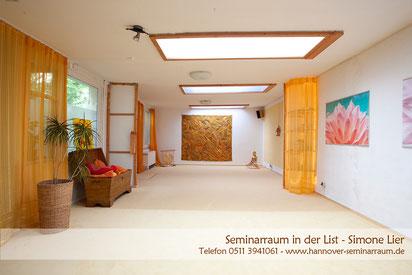 Lichtdurchfluteter Seminarraum mit hellem Teppich Korbmöbeln und Bildern in warmen Tönen