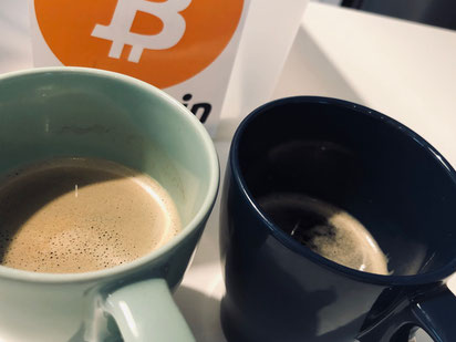 Kaffeetassen vor Bitcoin-Symbol