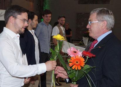 Junge Gesellen bekommen Blumen von Kreishandwerksmeister Konrad Zahn. Foto: Alpha-Report