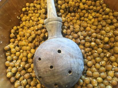 Oliven in einem Olivenfass mit Holzlöffel. Sizilianische Feinkost.