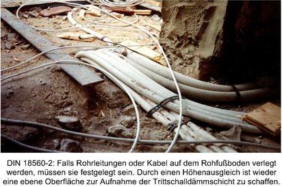 Foto eines Altbau-Roh-Fußbodens mit Rohrleitungen und Kabeln