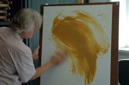 Cursist maakt grote gebaren een eerste opzet van zijn schilderij, met okerkleurige acrylverf op wit papier van 1 bij 0,7  m. De hand is onscherp door de snelle beweging.